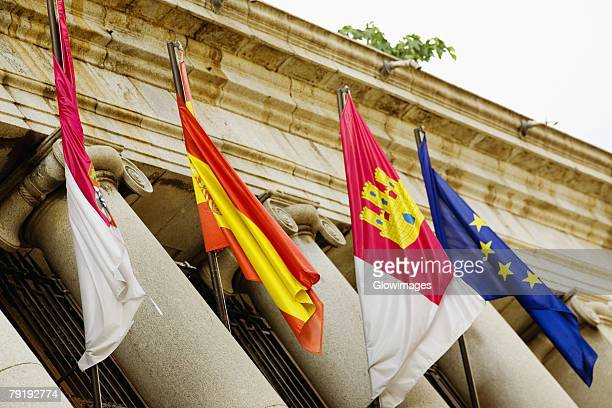 Low angle view of four flags on a government building, Toledo, Spain
