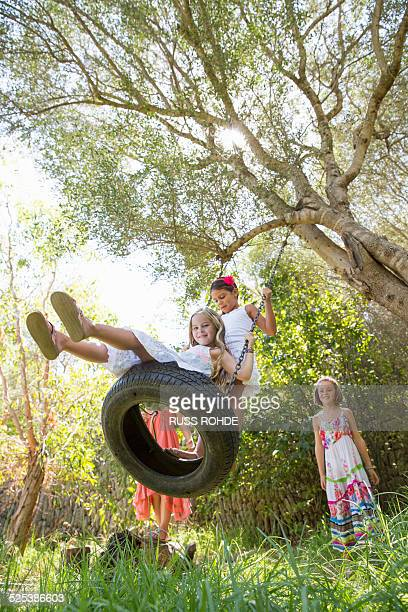 Low angle view of four girls playing on tree tire swing in garden