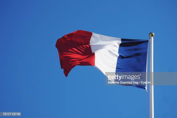 low angle view of french flag against clear blue sky - franse vlag stockfoto's en -beelden