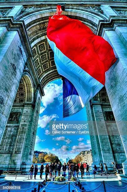 low angle view of french flag in front of arc de triomphe - champs elysees quarter stock pictures, royalty-free photos & images