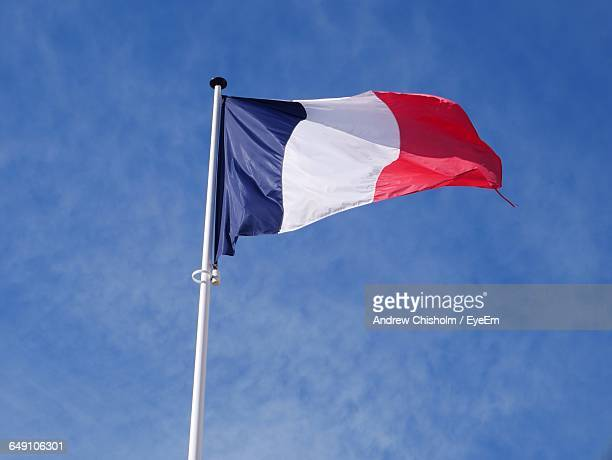 Low Angle View Of French Flag Waving Against Blue Sky