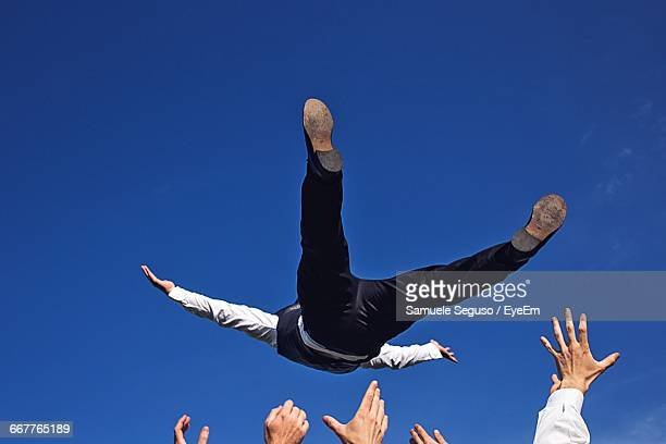 Low Angle View Of Friends Catching Groom Against Blue Sky