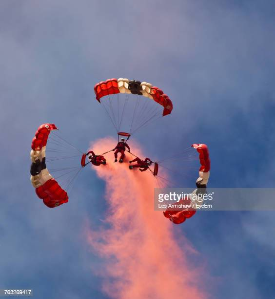 Low Angle View Of Friends Flying Parachutes Against Sky During Sunset