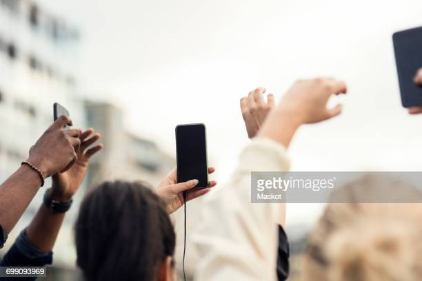 Low angle view of friends holding smart phones