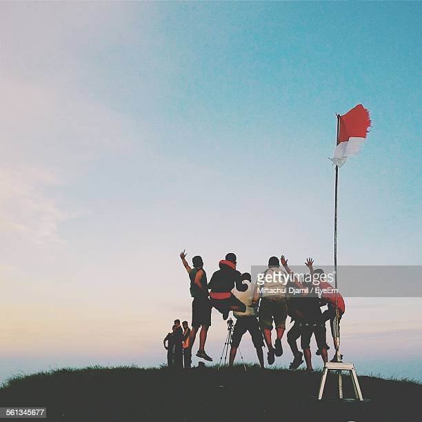low angle view of friends jumping on hill by indonesian flag at sunset - indonesia flag stock photos and pictures