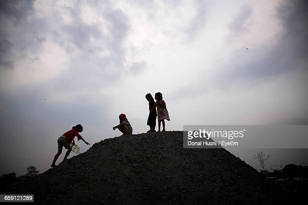 Low Angle View Of Friends On Cliff Against Cloudy Sky