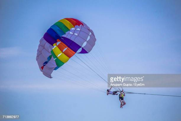 Low Angle View Of Friends Parasailing Against Sky