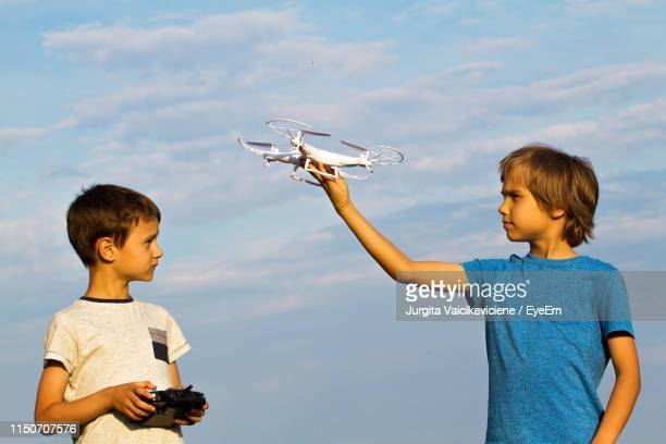 low angle view of friends playing drone while standing against cloudy sky - controllato a distanza foto e immagini stock