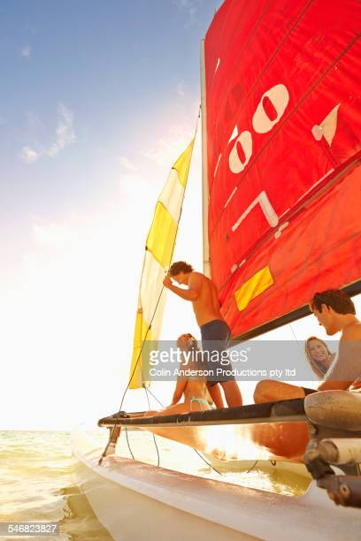 Low angle view of friends riding in sailboat on ocean