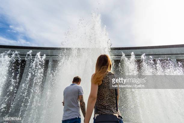 low angle view of friends standing by splashing water fountain - femme fontaine photos et images de collection