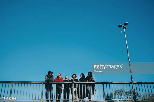 Low angle view of friends walking by railing on bridge