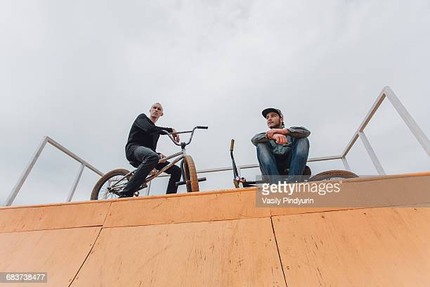 Low angle view of friends with bicycles on ramp against sky