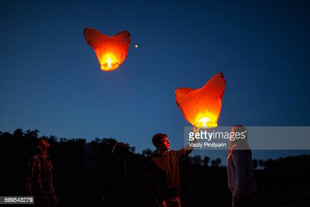Low angle view of friends with paper lanterns in forest