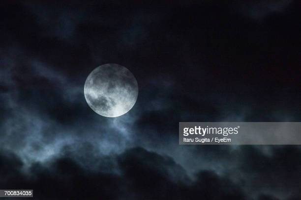 Low Angle View Of Full Moon In Cloudy Sky At Night
