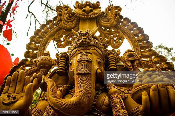 low angle view of ganesha statue against sky - hindu god stock photos and pictures