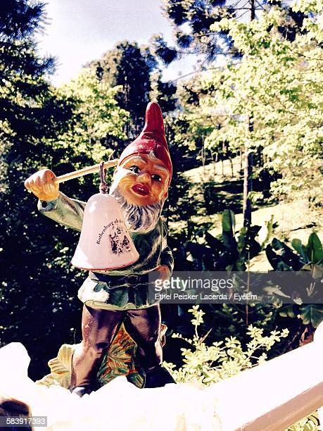 Low Angle View Of Garden Gnome Against Trees