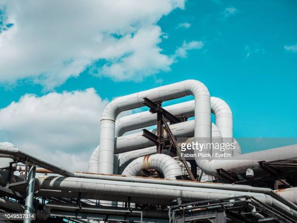 low angle view of gas pipes at industry against sky - pipeline stock pictures, royalty-free photos & images