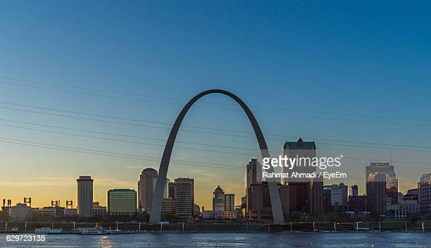 Low Angle View Of Gateway Arch And Cityscape By River Against Sky