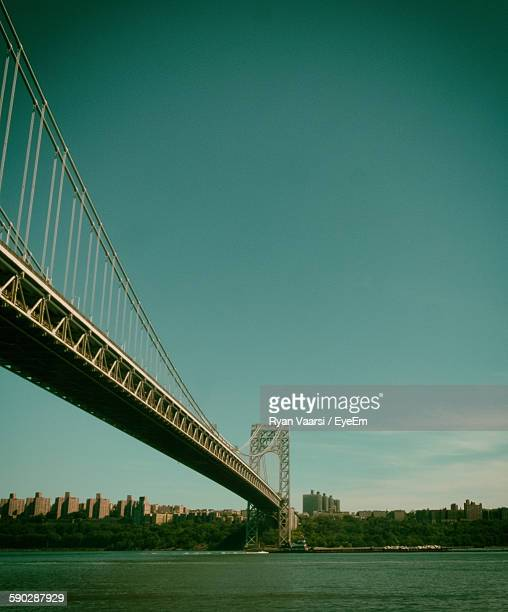 low angle view of george washington bridge over hudson river against sky - george washington bridge stock pictures, royalty-free photos & images