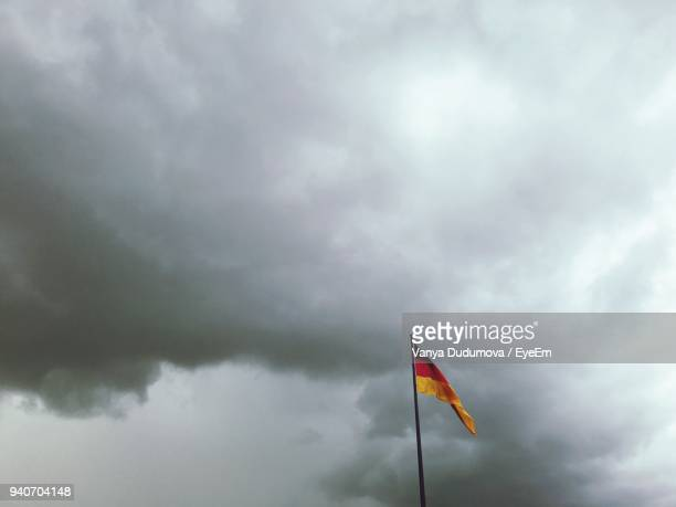 Low Angle View Of German Flag Against Cloudy Sky