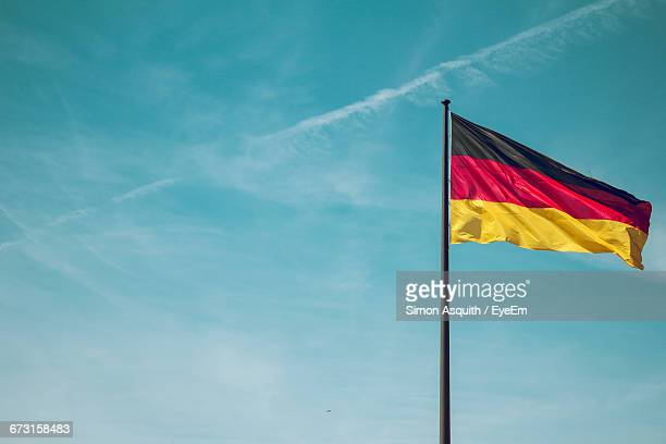 low angle view of german flag against sky - german flag stock pictures, royalty-free photos & images