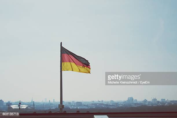 Low Angle View Of German Flag Fluttering Against Clear Sky