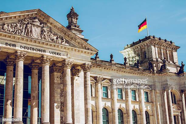 Low Angle View Of German Flag On Reichstag Building Against Clear Blue Sky