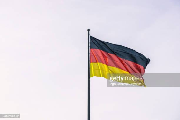 Low Angle View Of German Flag Waving Against Clear Sky