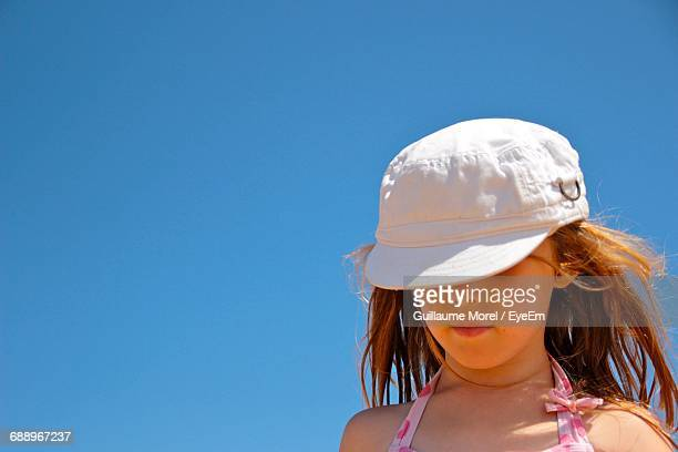 Low Angle View Of Girl Against Clear Blue Sky
