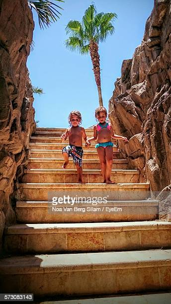 Low Angle View Of Girl And Boy Holding Hands While Moving Down On Staircase