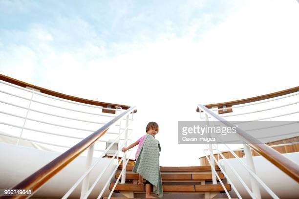 low angle view of girl climbing steps in cruise ship against sky - kreuzfahrtschiff stock-fotos und bilder
