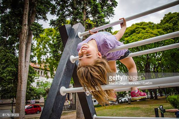 Low Angle View Of Girl Hanging On Structure At Park