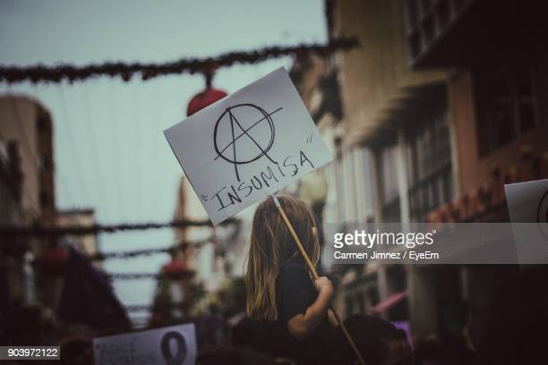 Low Angle View Of Girl Holding Placard In City