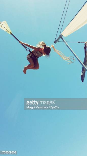Low Angle View Of Girl Jumping In Bungee Trampoline Against Blue Sky