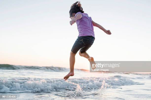 low angle view of girl jumping on waves at beach against clear sky during sunset - wet stock pictures, royalty-free photos & images