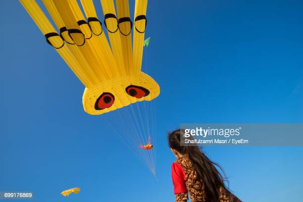 low angle view of girl looking at kite flying against clear blue sky - shaifulzamri eyeem stock pictures, royalty-free photos & images