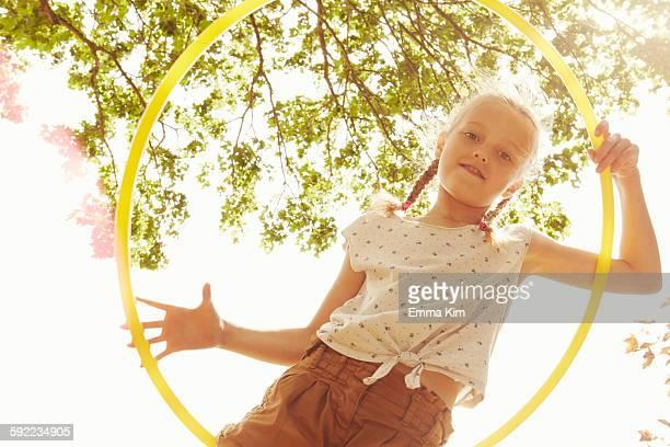 Low angle view of girl looking through hula hoop at camera smiling