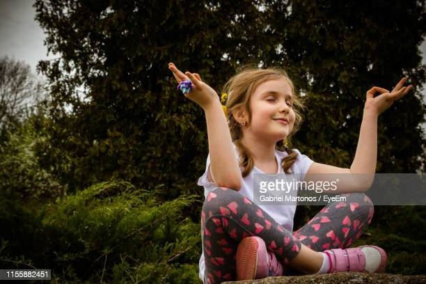 low angle view of girl meditating against trees in park - children only stock pictures, royalty-free photos & images