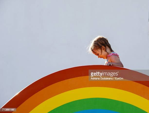 Low Angle View Of Girl On Top Of Rainbow Against Sky