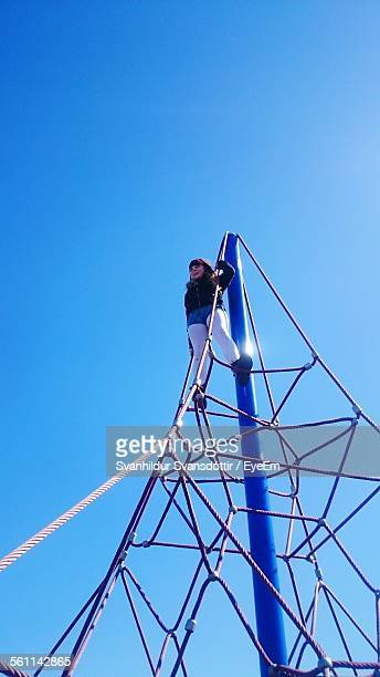 low angle view of girl on top of rope pyramid in park against clear blue sky - ジャングルジム ストックフォトと画像