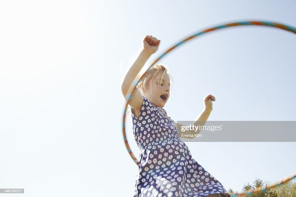 Low angle view of girl playing with plastic hoop : Stock-Foto