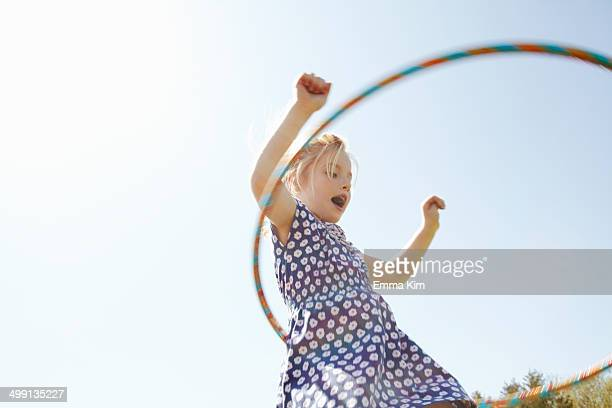 Low angle view of girl playing with plastic hoop