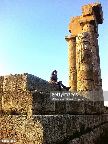 Low Angle View Of Girl Sitting At Acropolis Against Sky