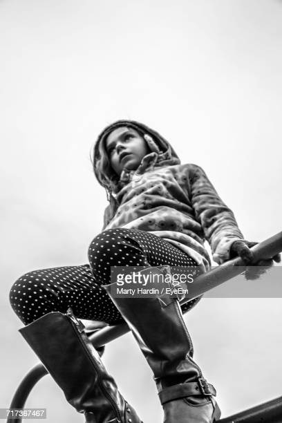 low angle view of girl sitting on metallic structure against clear sky - marty hardin stock photos and pictures