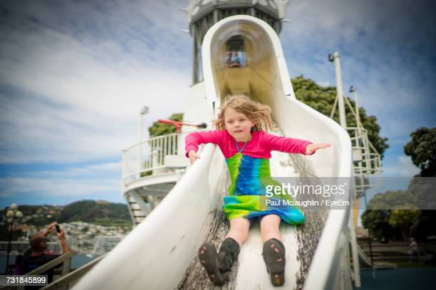 Low Angle View Of Girl Sliding On Slide At Playground Against Sky
