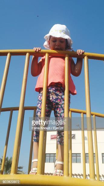 low angle view of girl standing on play equipment against clear sky - elena knouzi stock pictures, royalty-free photos & images