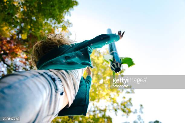 low angle view of girl throwing toy rocket skyward from garden - heshphoto stock pictures, royalty-free photos & images