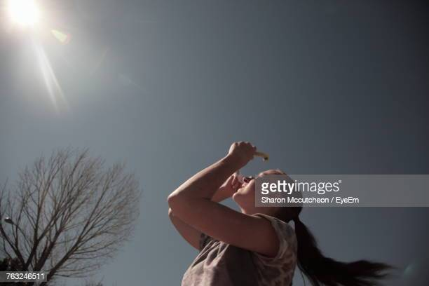 Low Angle View Of Girl Watching Solar Eclipse