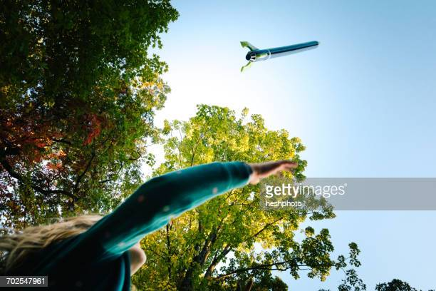 low angle view of girl watching toy rocket flying toward blue sky - heshphoto stock pictures, royalty-free photos & images
