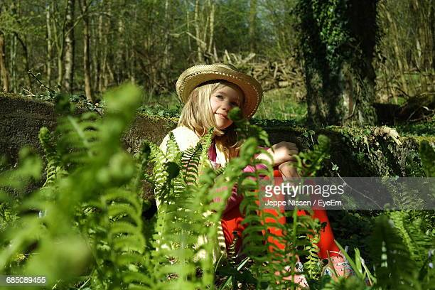Low Angle View Of Girl With Hat Sitting Amidst Plants In Forest